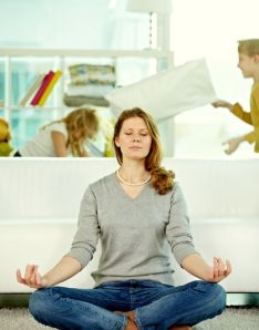 Mother meditating in lotus position with children playing in the background