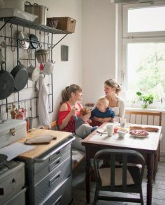 Young mothers  with babies (6-12 months) talking in domestic kitchen